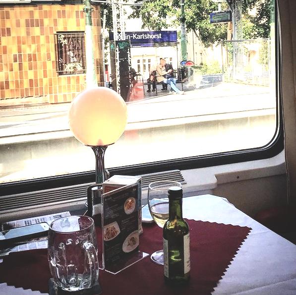Wein und Bier im tschechischen Speisewagen. Im Hintergrund: Der Bahnhof Berlin-Karlshorst